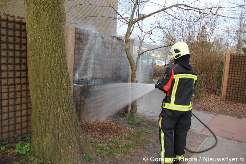 Brandweer blust brandende schutting