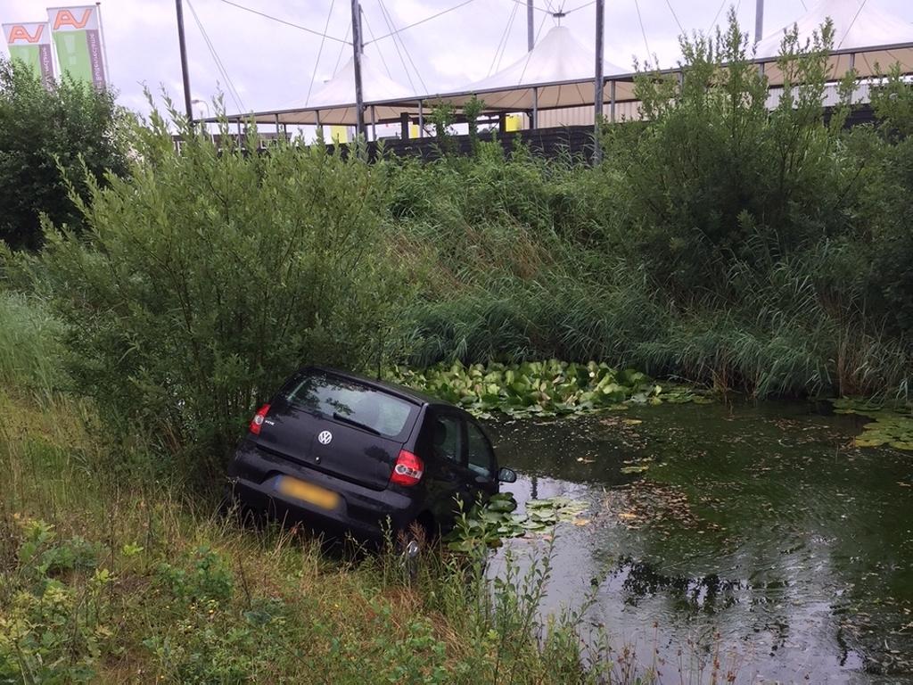 Automobilist met zijn voertuig te water aan de Nijverheidsweg in Assen